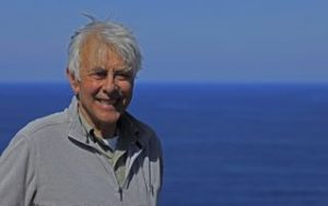 photo of John Philip Busby with blue sea and sky behind